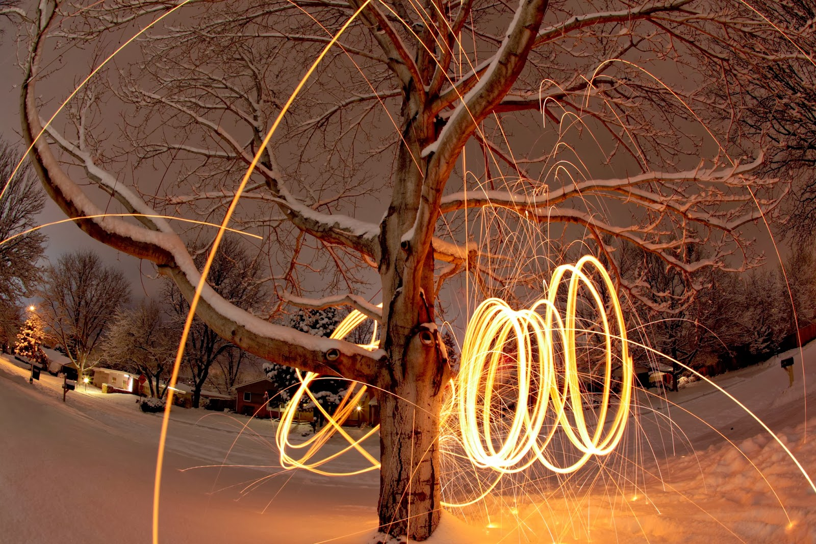 Spinning some burning steel wool by a tree in a snowy front yard.