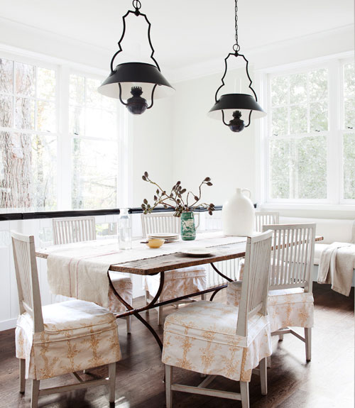 Breakfast nook with black pendant lights and a wood table surrounded by white chairs with upholstered seats
