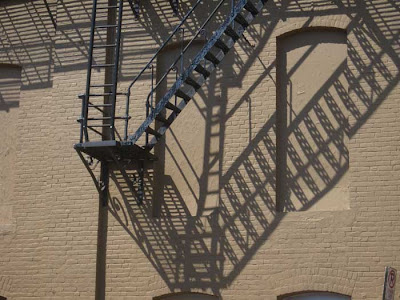 Shadows of fire escapes on a brick building
