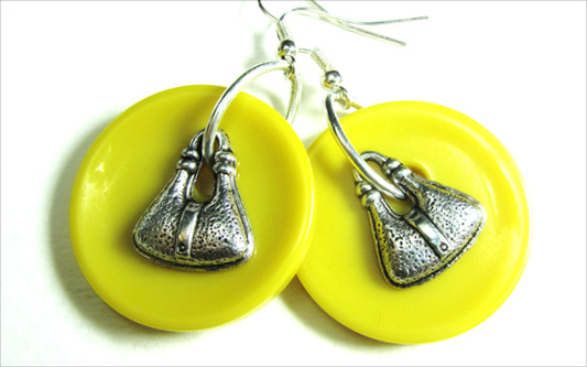 Drop dangle earrings have silver handbag charms over yellow fashion buttons