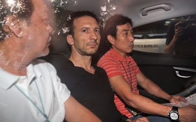 Belgian national Philippe Graffart (center) arrives at the state court in Singapore.