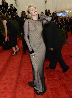 Miley Cyrus strikes a provocative for cameras at  2013 Met Gala red carpet