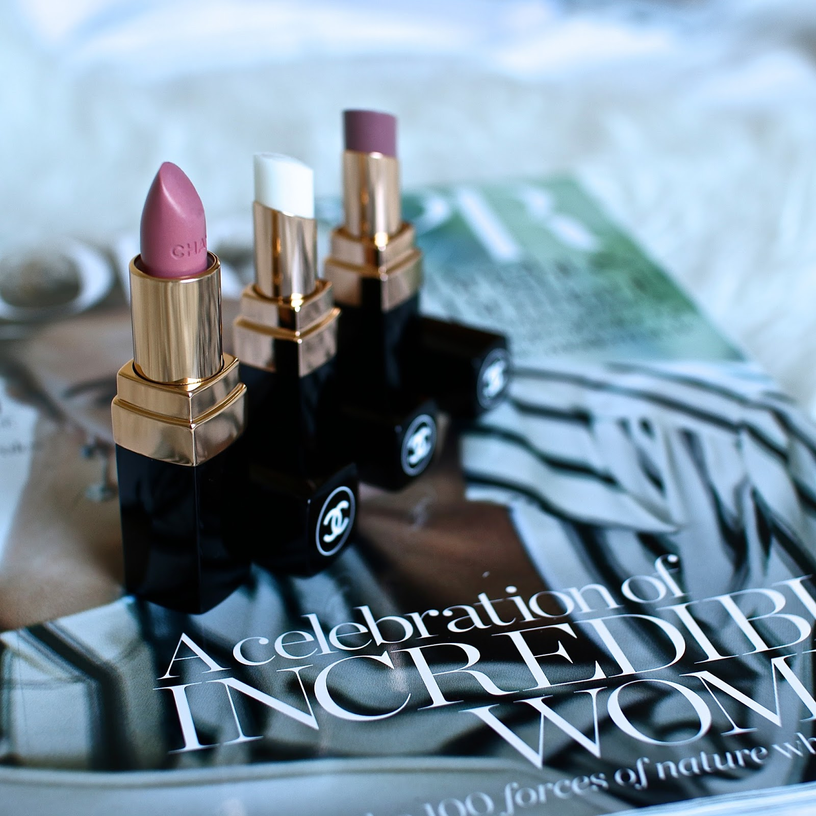 3 neutral coloured Chanel lipsticks sitting in a row on top of a Bazaar magazine