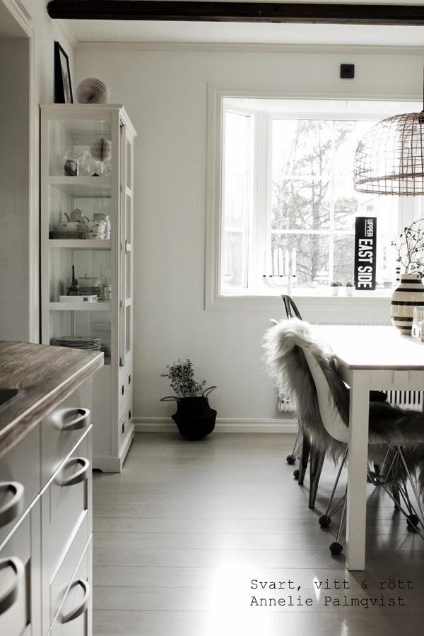 interiör, interior, inredning, vitt, vitmålade väggar, sephora, grön växt, snygg blomma, svart ricekorg, afroart, inredningsdetaljer, detaljer, details, home, vitt vitrinskåp, skåp med glasdörrar, korglampa, svart plåtskylt med vit text, svartvitt, matsalsbord, stolar matbord, fårskinn, kök, kitchen