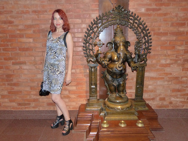 Animal prints dress, chunky heel shoes; Ganesh sculpture
