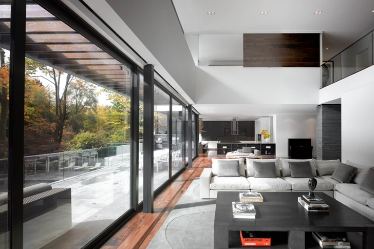 Living room with glass wall in Modern mansion by Belzberg Architects Group