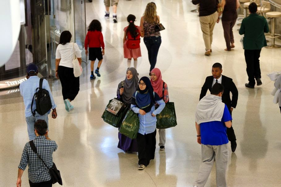 In this Friday, June 20, 2014 photo, people walk around a shopping mall in west London. London has long attracted big spenders. But every year around the holy month of Ramadan, which starts this weekend, a surge of spectacularly rich Middle Eastern shoppers arrive and take retail therapy to a whole new level _ complete with an entourage of bodyguards, chauffeurs, and Gulf-registered Rolls-Royces and Ferraris flown in just for the occasion. It's a huge and growing market for British shops, luxury hotels and restaurants, and many welcome the big spenders with exclusive products and VIP services like translators and personal shopping managers.