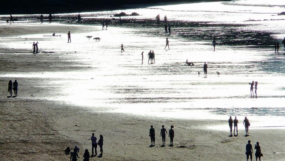 gente pasenado en la playa de sopela