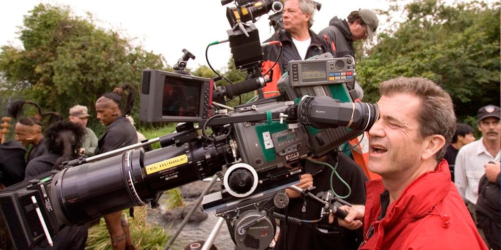 mel gibson como diretor no set de apocalipto operando uma camera cinematográfica enqunto sua equipe permanece no entorno