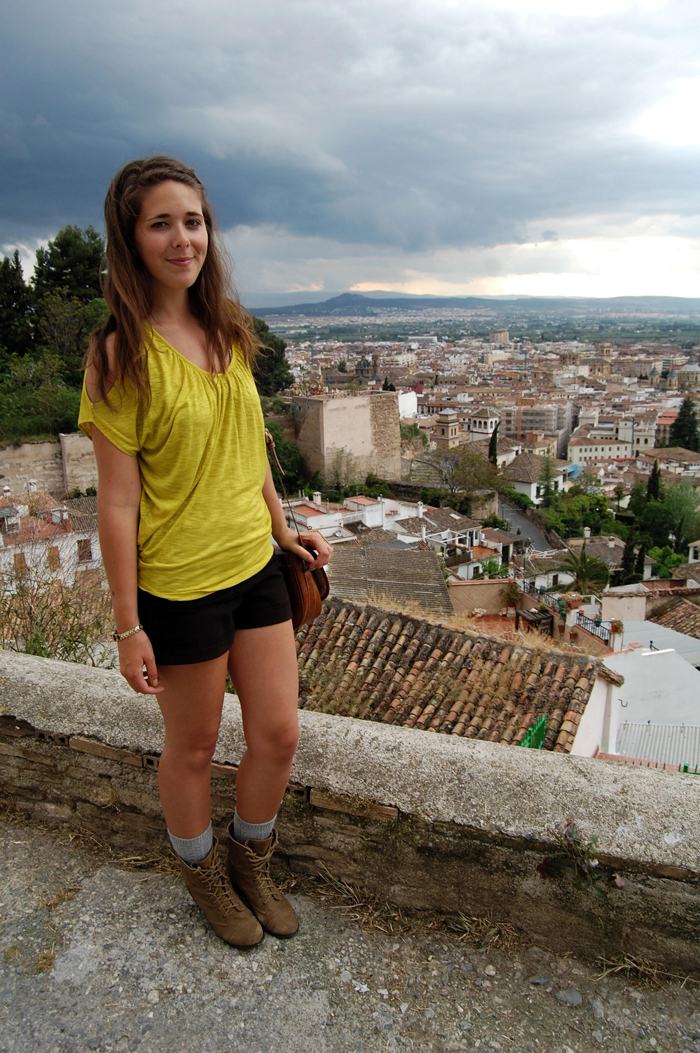 Chartreuse bouse worn with black shorts, gold armband, leather bag and combat boots looking over Granada, Spain.