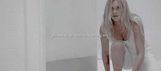 """Clarke (personagem de The 100) abaixada olhando atenta para algo fora da imagem, os cabelos loiros estão caídos desajeitados cobrindo a maior parte do rosto e seu braço tem um corte sangrento. Ela parece que está em movimento. Está vestindo um short e uma camiseta brancos. O cenário de fundo é de paredes brancas. Em cima da imagem um texto """"por favor pare, você está me assustando"""""""