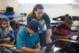 Teacher assisting student using Chromebook