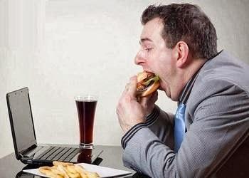 خمسة انواع من الاطعمه لحماية مستخدمى الكمبيوتر  - رجل يأكل اما الكمبيوتر لابتوب - man eating using computer laptop