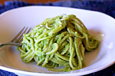 pasta tossed with avocado sauce in a white bowl