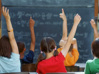 Image of young students raising their hands in a classroom.
