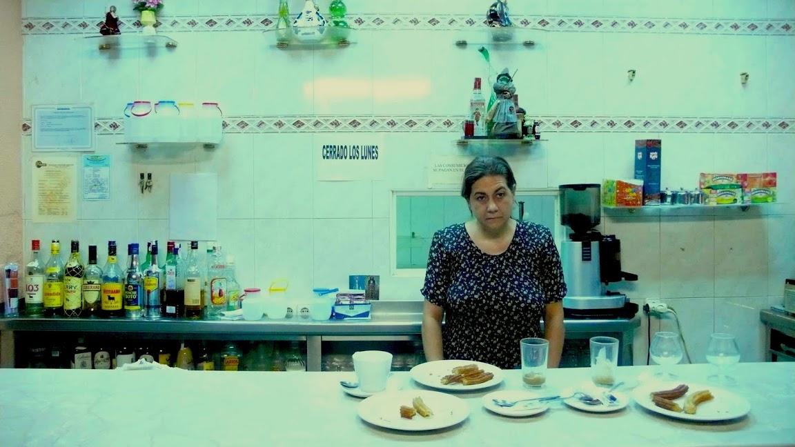 fotograma con la actriz Luisa Martín tras el mostrador del bar. en la imagen se potencian los tonos verdes