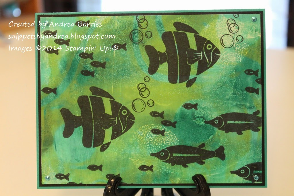 Ocean-like background created with shades of blue and green acrylic paint and a gel printing plate. Stamped with fish images and mounted on a card base.