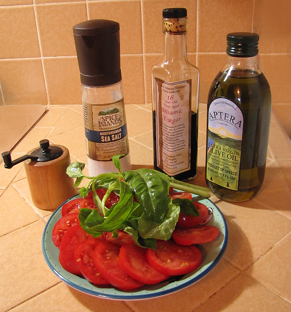 Bottles of Balsamic Vinegar, Olive Oil, Salt, Pepper and Plate of Tomatoes and Basil