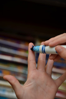 marking a dot on a finger for finding a letter in the environment