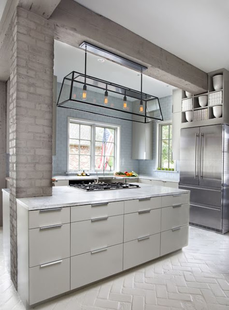 kitchen with painted gray columns with white cabinets and silver french door fridge