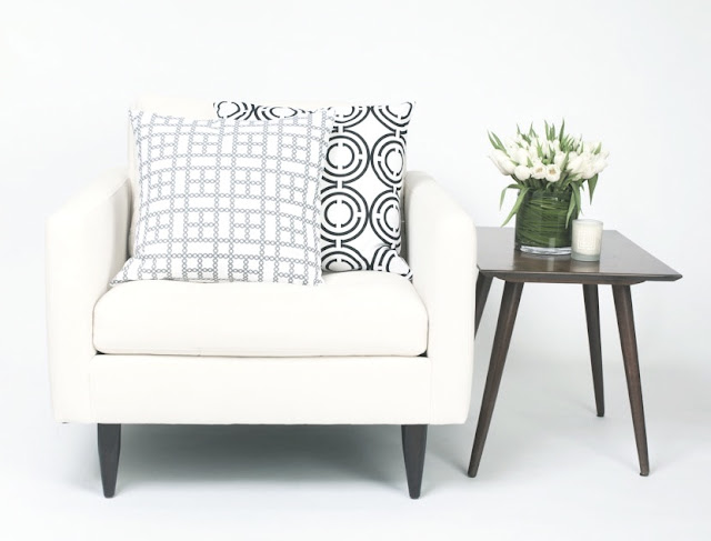 COCOCOZY Light pillows on a white chair with a wood accent table holding white tulips and a candle