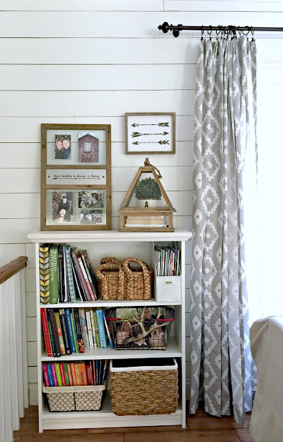 Ikea Billy bookshelf with trim added in front of plank wall with Target Aztec drapery panels - www.goldenboysandme.com
