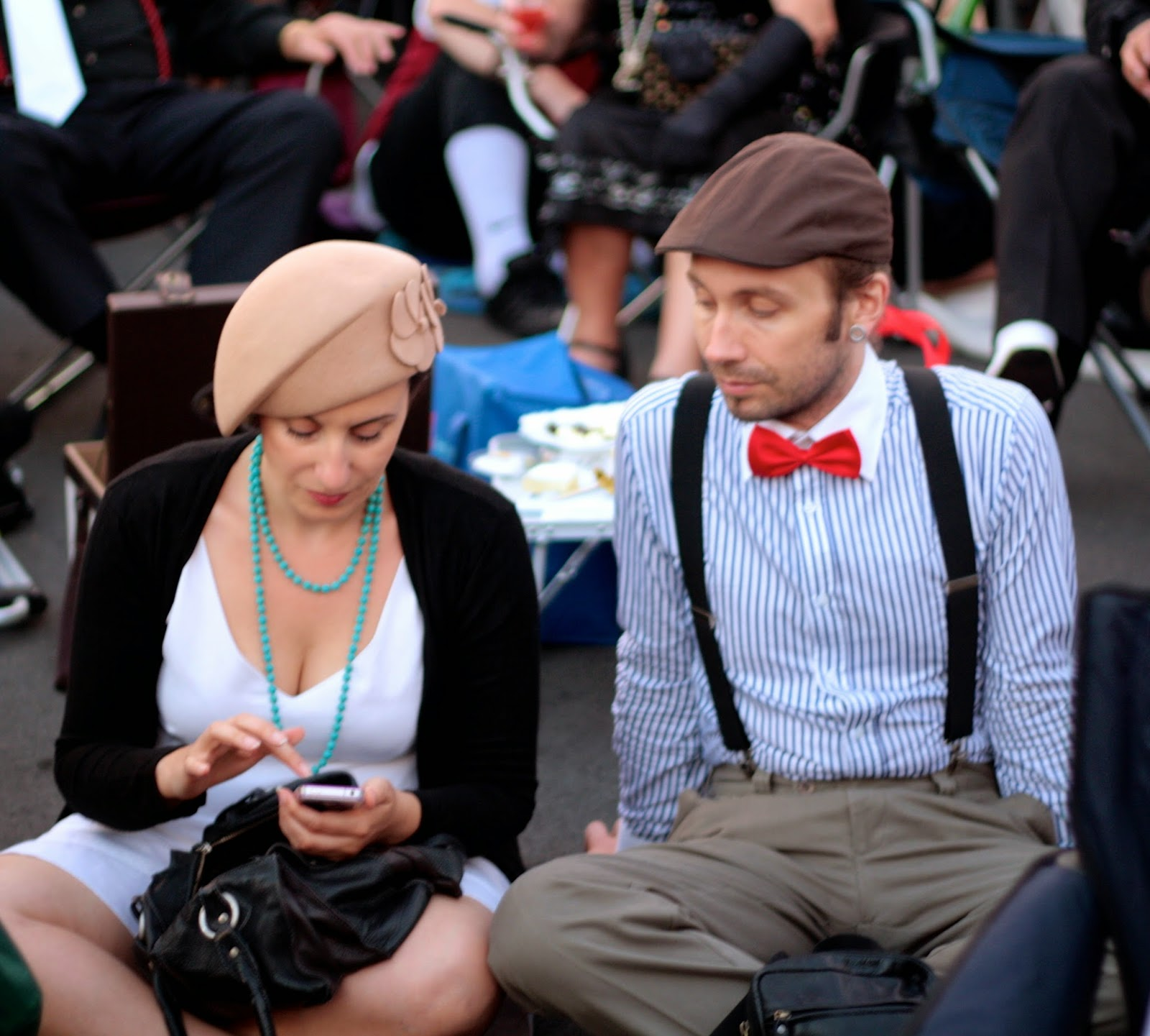 An art deco couple sends a text on an iPhone.