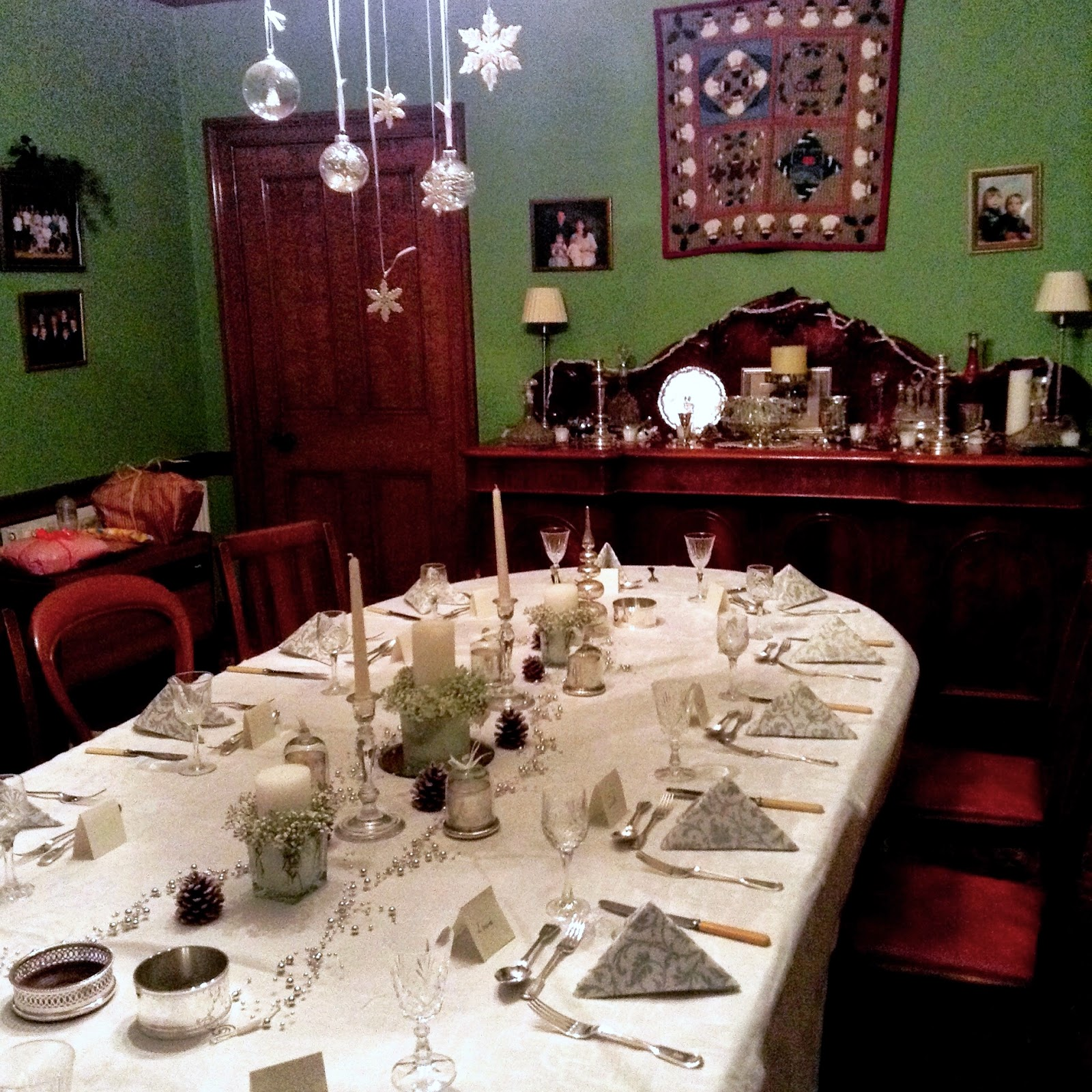 Christmas dinner table with white & silver napkins, candles, pine cones & dangling ornaments on light fixture