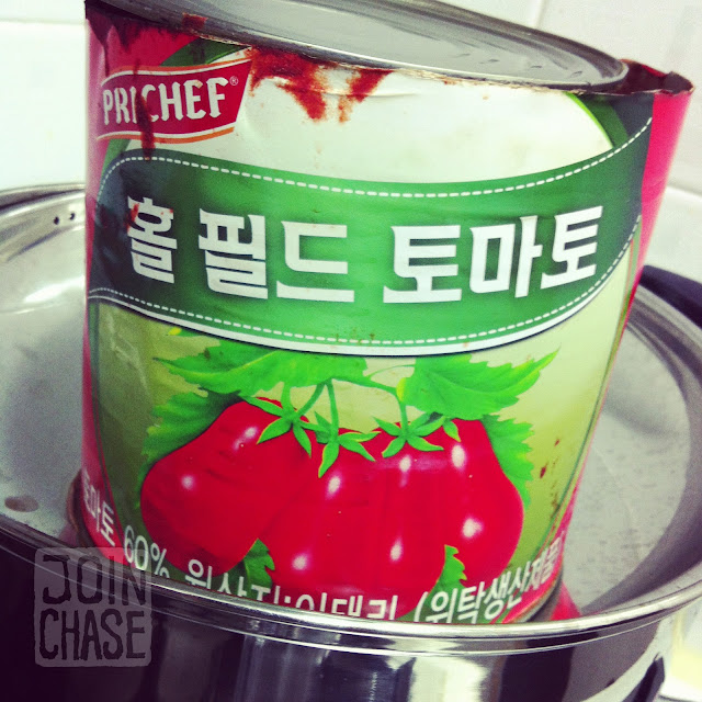A large can of whole peeled tomatoes with Korean written on the label.