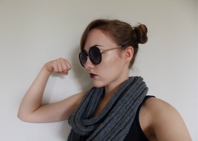 Fiona C. (An Honest Drug) poses against an off white background, wearing a black tank top, a grey snood, and round black sunglasses. She faces the left, and flexes her arm in a rosie the riveter pose.
