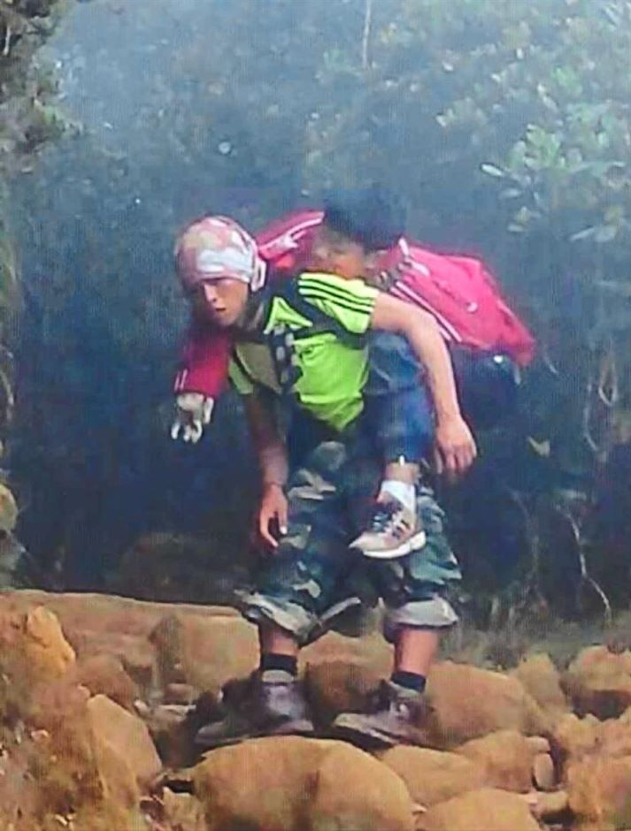 A thousand words: The iconic image of Rizuan carrying the injured boy.