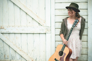 Picture shows a woman standing to the right of a barn door holding a guitar in her right hand and wearing a fedora hat and a white summer dress.