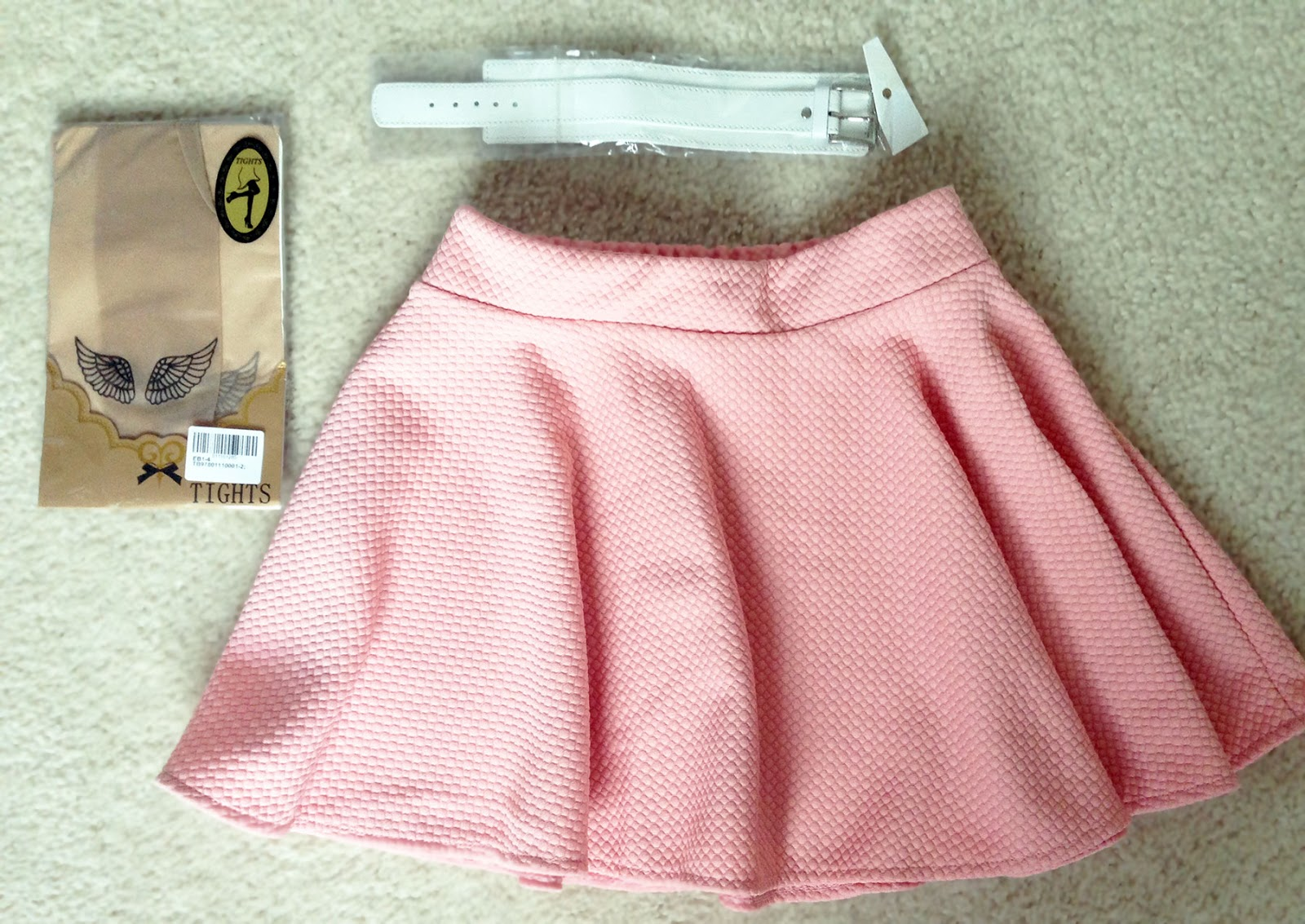 Chicnova pastel pink pure color skater skirt, white leather bracelet, and tattoo printed tights laid out on carpet