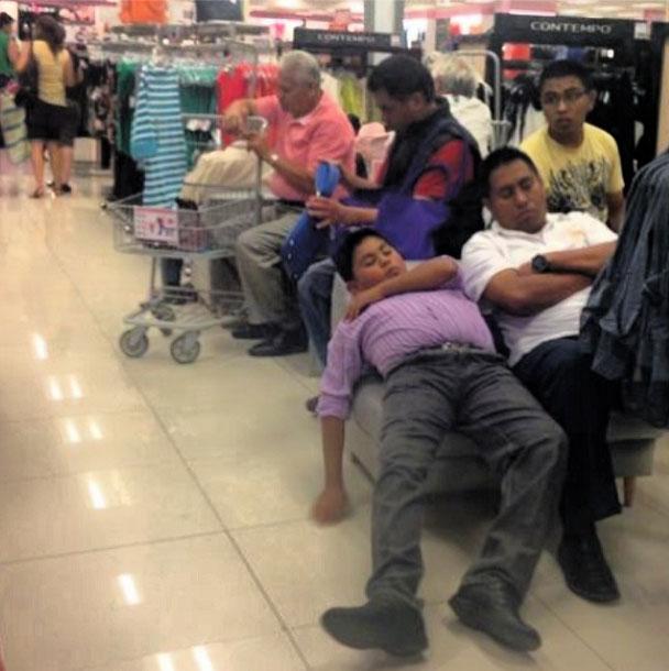 Hombres aburridos de compras con su mujer
