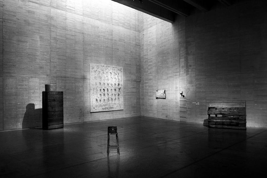 Sala com um banco no centro, alguns objectos de mobiliário junto às paredes, dois quadros na parede.