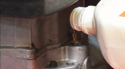 close up of pouring oil into a lawnmower