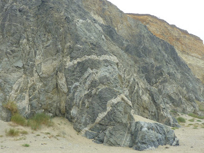 Tortured whilte dikes cutting through granitic rock