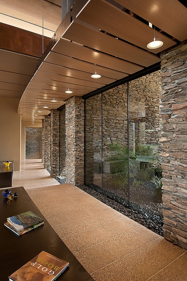 Stone and glass walls in the Sefcovic Residence by Tate Studio Architects