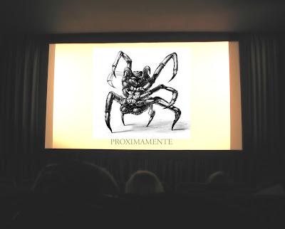 En un sala de cine se ve proyectado el parásito.