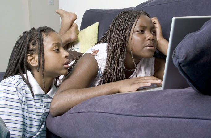 Siblings staring at laptop screen