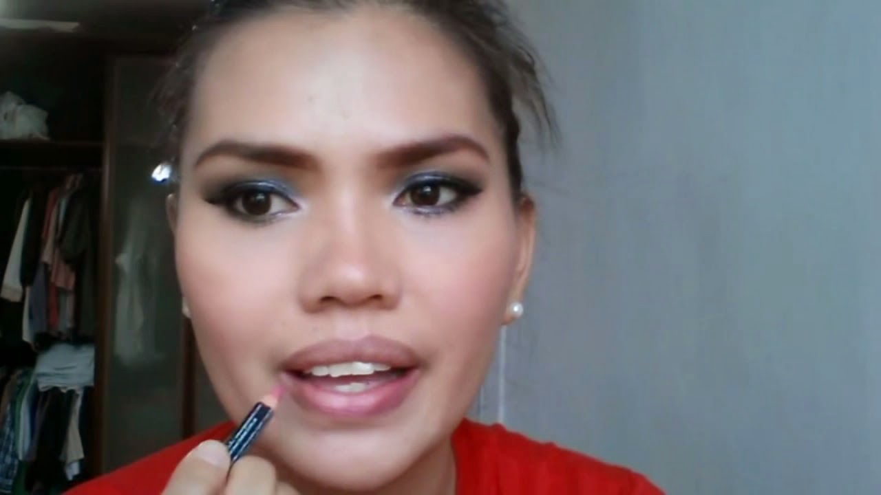 Black Smokey Eyes Makeup Tutorial. Lady putting lip liner in pink