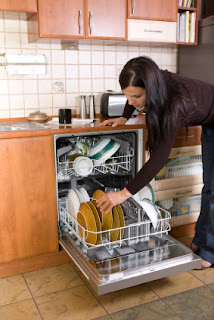 Woman loading the dishwaster