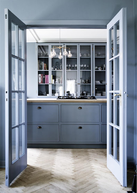 blue kitchen with herringbone wood floors