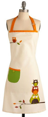 an owl themed apron hanging on a manequin