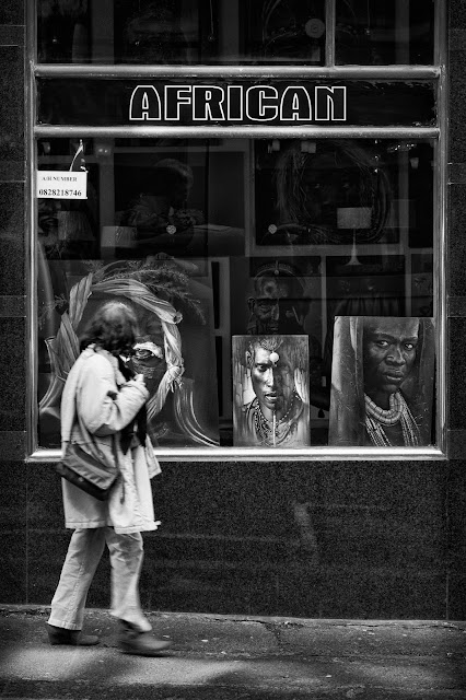 A woman walks past a shop window displaying African works of art