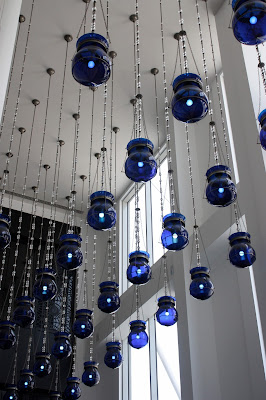 rows of blue lightbulbs hang from a high white ceiling in front of open windows