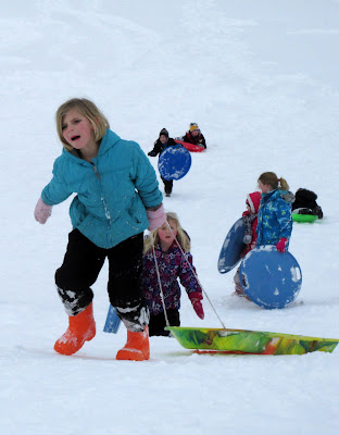 Kids climbing up a sledding hill
