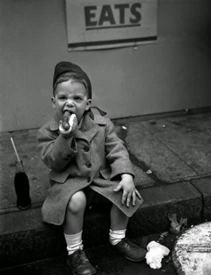 boy-eating-hot-dog-pavement