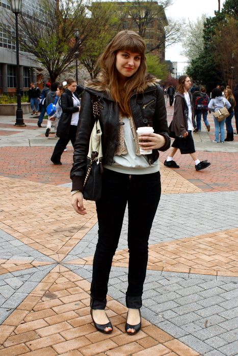 Virginia Commonwealth Student wears a leather jacket over a cream knit tip and black slim jeans with black peep toe heels.