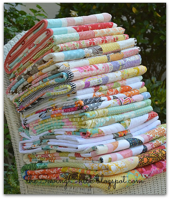 a folded stack of colorful modern quilts